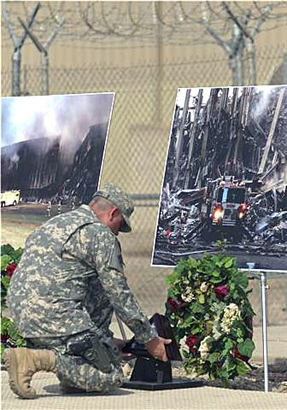 Army Command Sgt. Maj. John Gioia kneels down to place a flag that was flown at…