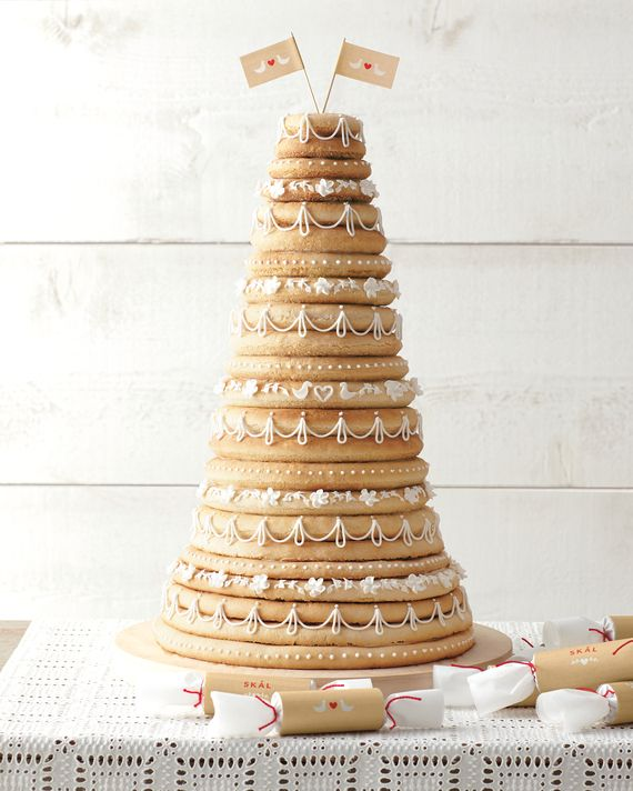 "Rare is the Norwegian or Danish couple that says ""I do"" without serving a kransekake, which means ""wreath cake."" The tasty tower has been around since the 1700s and consists of concentric rings of marzipan biscuit topped with party crackers or flags. The bride and groom pull off the top rings with their hands in a customary scandinavian ring-breaking ceremony; the number of layers still attached predicts how many kids they'll have. Our kransekake makes a modern statement with intricate…"