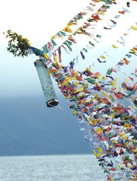 "The people of Nishinoshima construct great Shaara-bune straw ""spirit ships"" with a coiled prow ornament representing an elephant trunk (Buddhist symbols) for the send-off (of spirits) rite on last day of O-bon. Kids prepare thousands of little paper prayer flags which they carry around from house to house to be inscribed to Buddha. Kids are rewarded by sweets at the homes memorializing the first Bon after a death. These so-called tsuzuki-bata are strung together and suspended to simulate…"