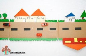 A cardboard road made from a box is a fun DIY toy for kids. Cut out trees and houses on the outer edges and paint them in vibrant colors.   at Non Toy Gifts