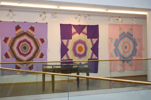 Quilt exhibit at Central Library displaying Polly Bennett's handmade quilts.