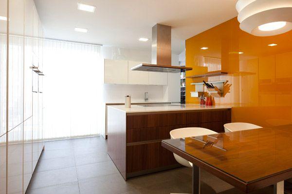 Cocina blanca y luminosa, con gran pared de cristal naranja dando un ...