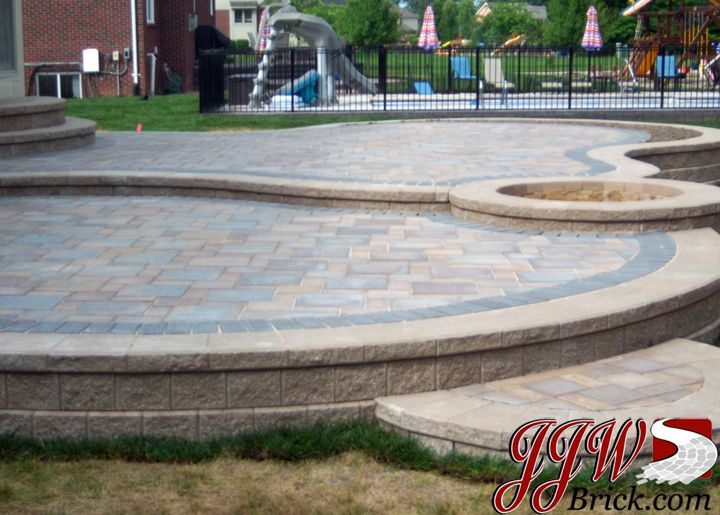 2 tier paver patio design with built in fire pit between 2 levels unilock - Patio Brick Designs