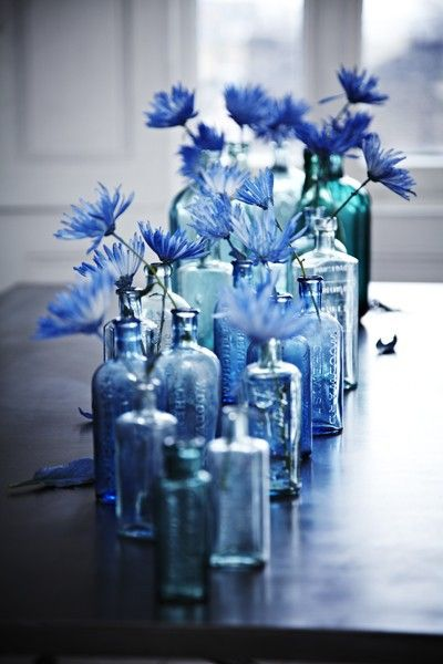 Similar bottles are filled with flowers and displayed along the length of a table, serving as a eye-catching centerpiece