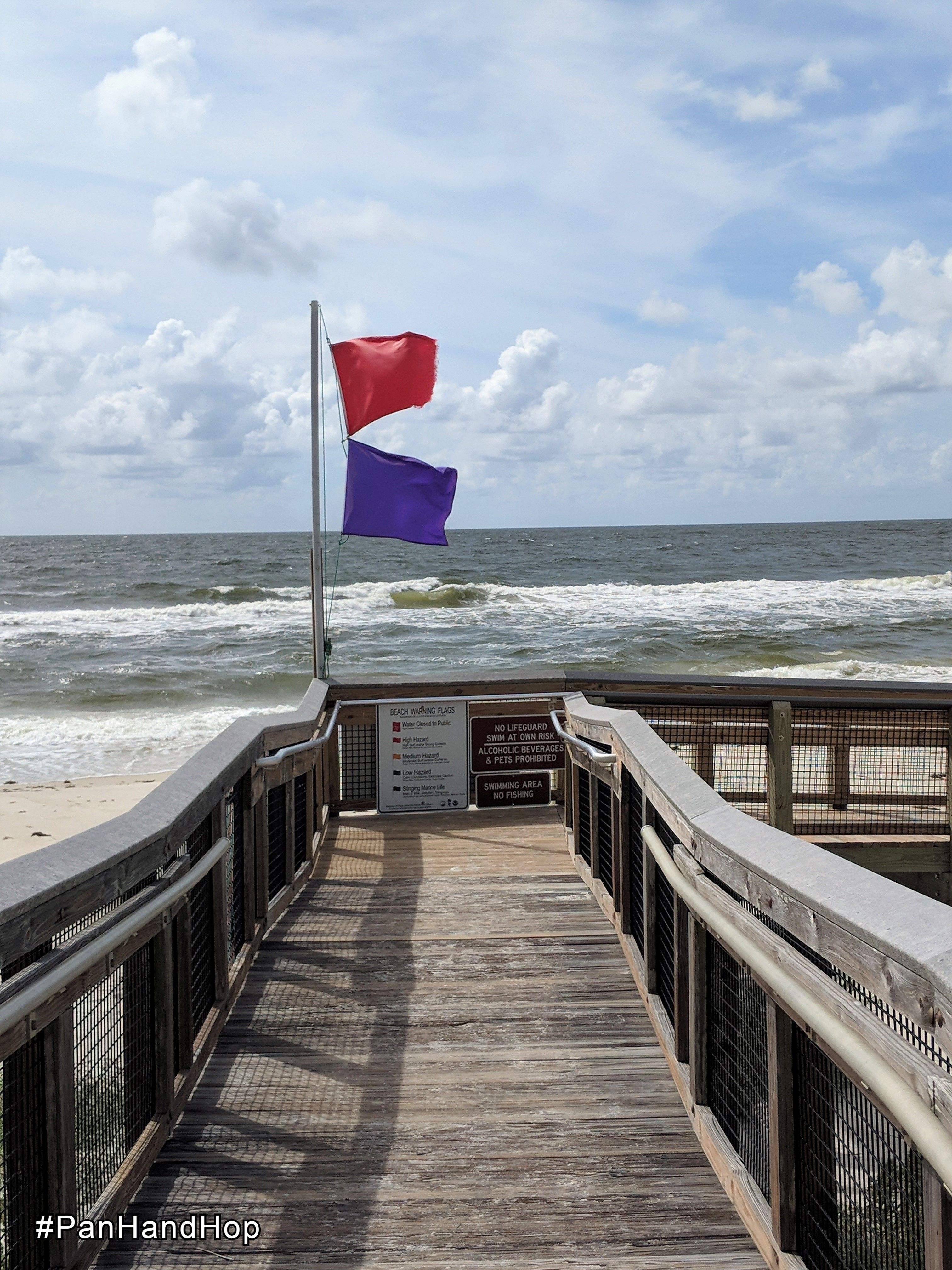 Boardwalk with flags showing hazardous surf and jellyfish warnings