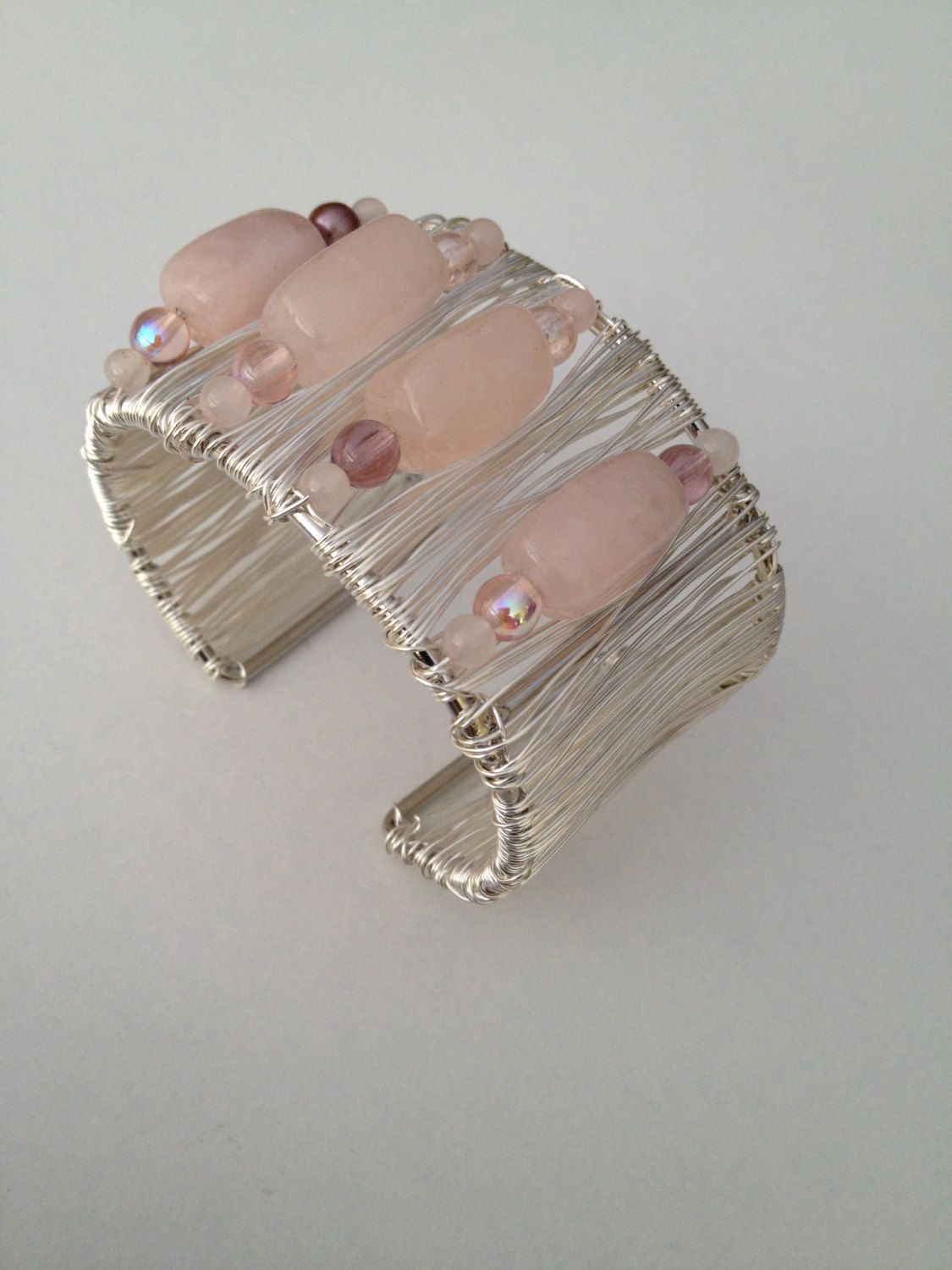 "Handmade Silver Wire wrapped Vintage style Cuff Bracelet. This is a chic, feminine cuff bracelet that will soon become one of your favorite pieces of jewelry. The Silver color artistic wire is non tarnish and hand wrapped onto a cuff form. The large oval shape beads are a very soft pretty pink opal look stone. The beads are wrapped across the front of the cuff bracelet onto the bracelet. Cuff measures approximately 2.5"" wide and adjusts to any wrist. ..."