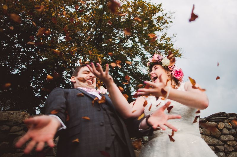Stunning bride and groom throwing orange and yellow leaves in Autumn / Fall. Bride wearing a wonderful flower crown too!