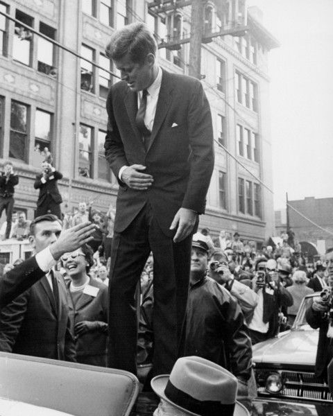 JFK standing in his car