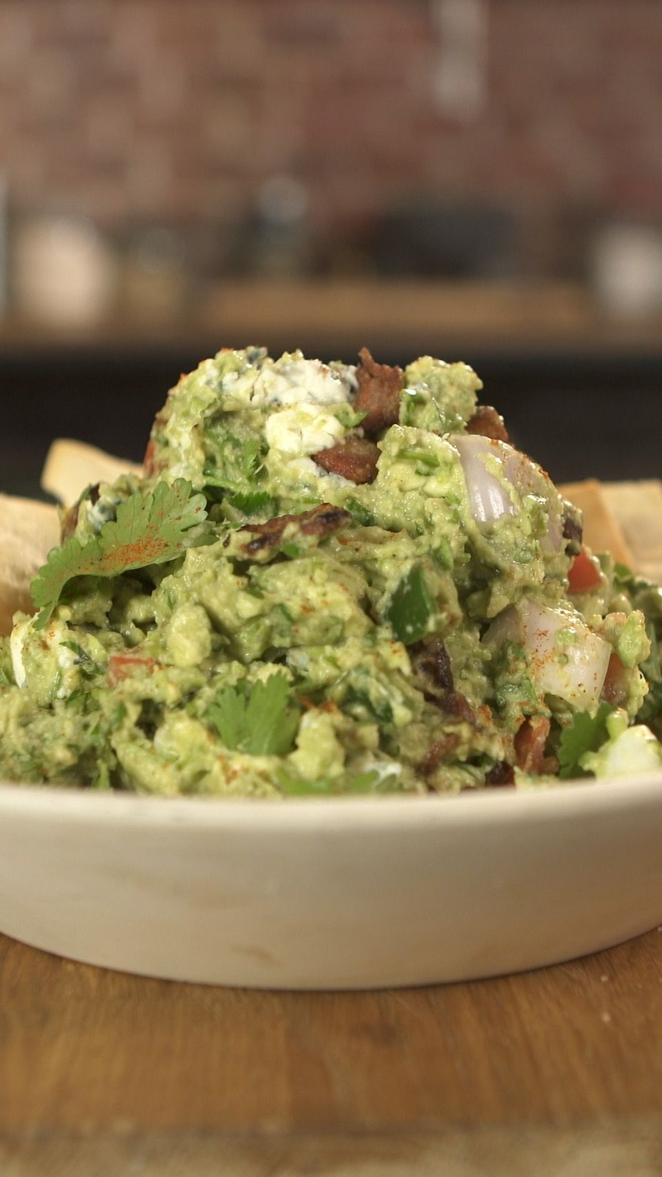 Recipe with video instructions: Marcus is bringing you his take on Guacamole.   Ingredients: 4 Haas Avocados, 2 limes juiced, Kosher salt, 1/2 tsp cumin, 1/2 tsp cayenne, 1 shallot, diced, 1 jalapeno, diced, ¼ c bacon, diced, 2 medium roma tomatoes, seeded and diced, ½c chopped cilantro, 1 clove minced garlic, 2 Tbsp smoked blue cheese