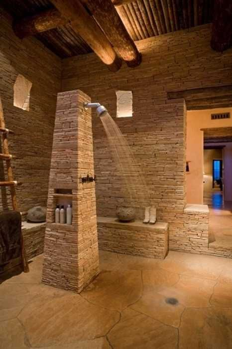 stone and wood bathroom design with open shower stone bathtub and fireplace