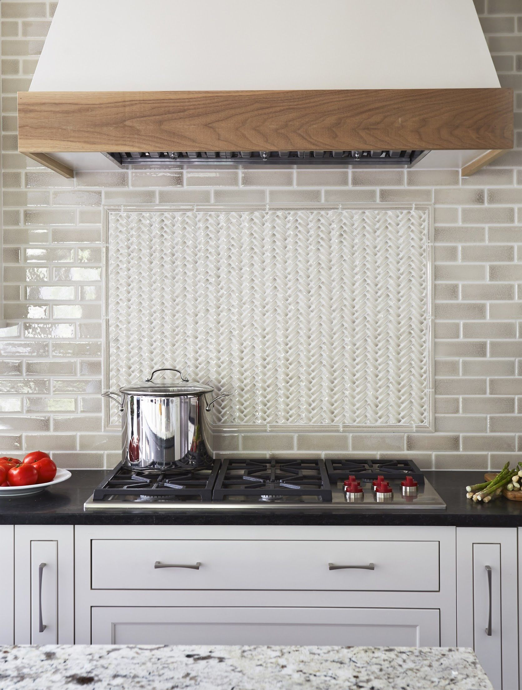 Soft white inset cabinets paired with a slate gray island provide a ...