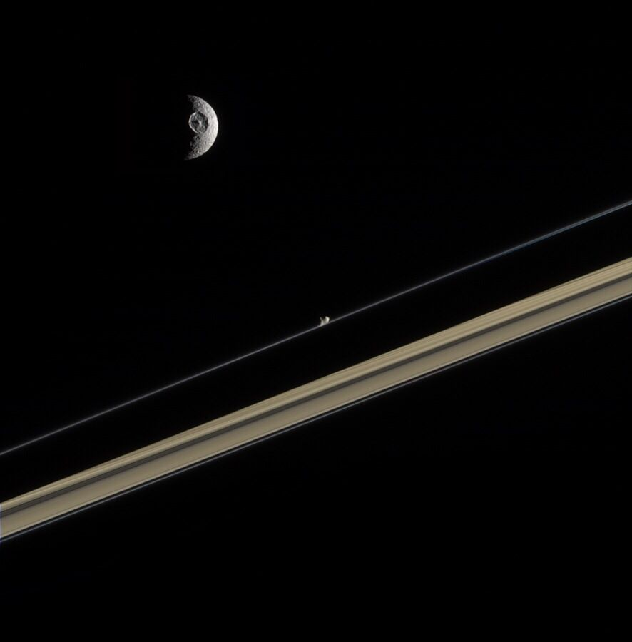 Mimas, its crater Herschel and Prometheus in Saturn's rings.