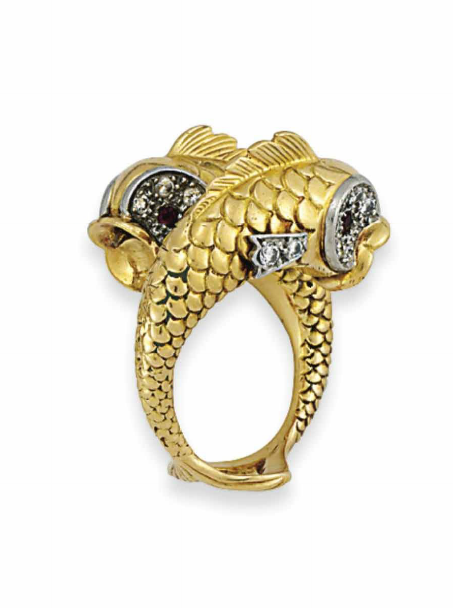A NOVELTY RING, BY BOUCHERON Modelled as a pair of leaping fish, with pavé-set ruby and diamond cluster eyes, diamond fins and engraved scale detailing, 1960s, rubbed French marks for gold, finger size M Signed Boucheron, Paris, no.49180