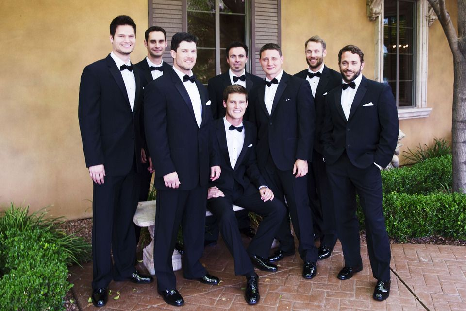 groom groomsmen posing in their black tuxedos with their bowties