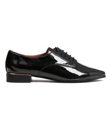 Musta. Teräväkärkiset derby-kengät kiiltävää tekonahkaa. Avoimet nauhaläpät. Korossa metallinvärinen koriste. Vuori ja pohjallinen tekonahkaa. Kumipohja ja