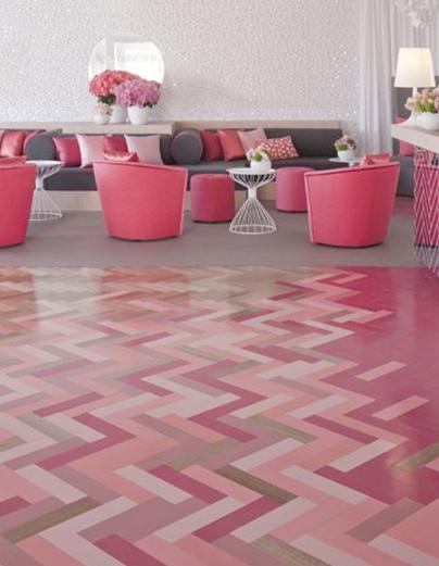Pink hued herringbone pattern in floor with pink chairs