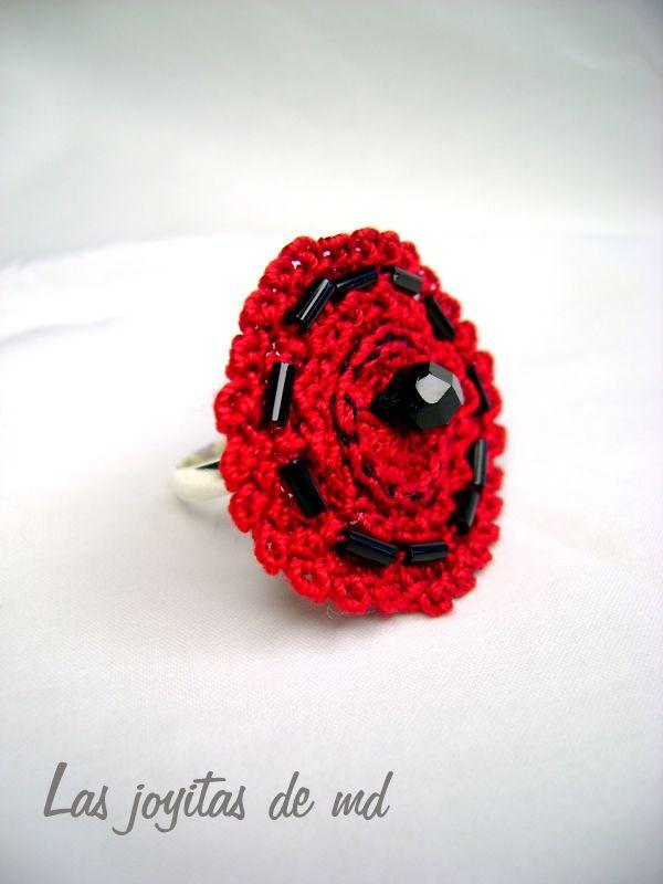 Anillo de croché. Rosetas rojas decoradas con canutillos y piedra de swarovski negra.