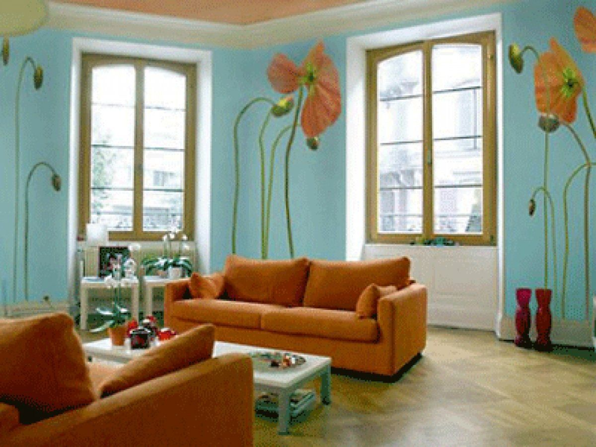 Contemporary Apartment Living Room With Soft Blueish Wall Color And Vibrant Orange Sofa Flower