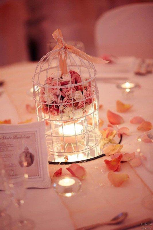 decoration centre de table avec cage a oiseau blanche boule de fleurs lysianthus oeillet mini rose et petales parsemees