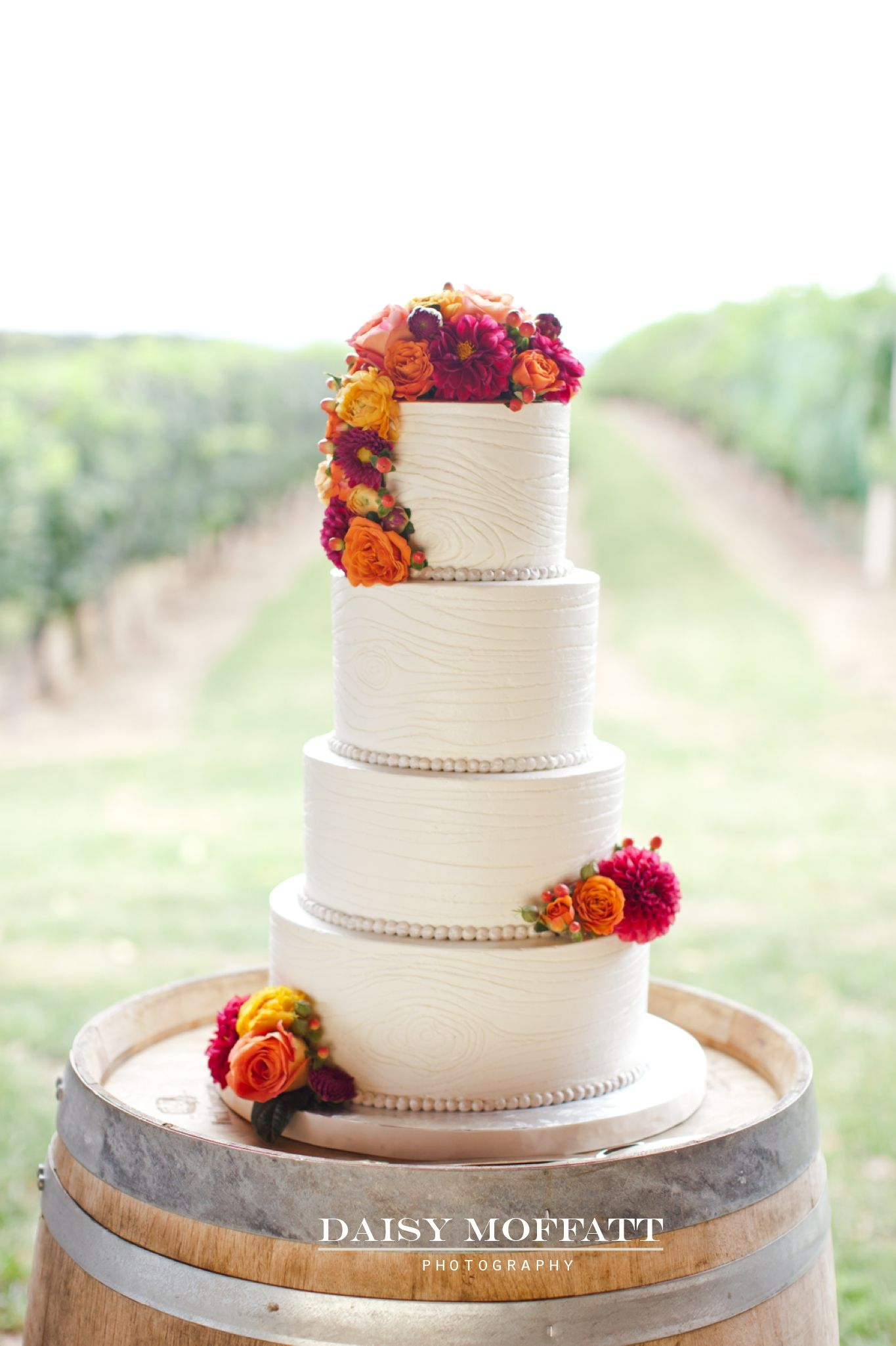 Vineyard wedding cake with wood grain frosting by @Jennifferwhite . Coral and pink. Very yummy! #weddingcake #vineyard #wedding www.daisymphotography.com