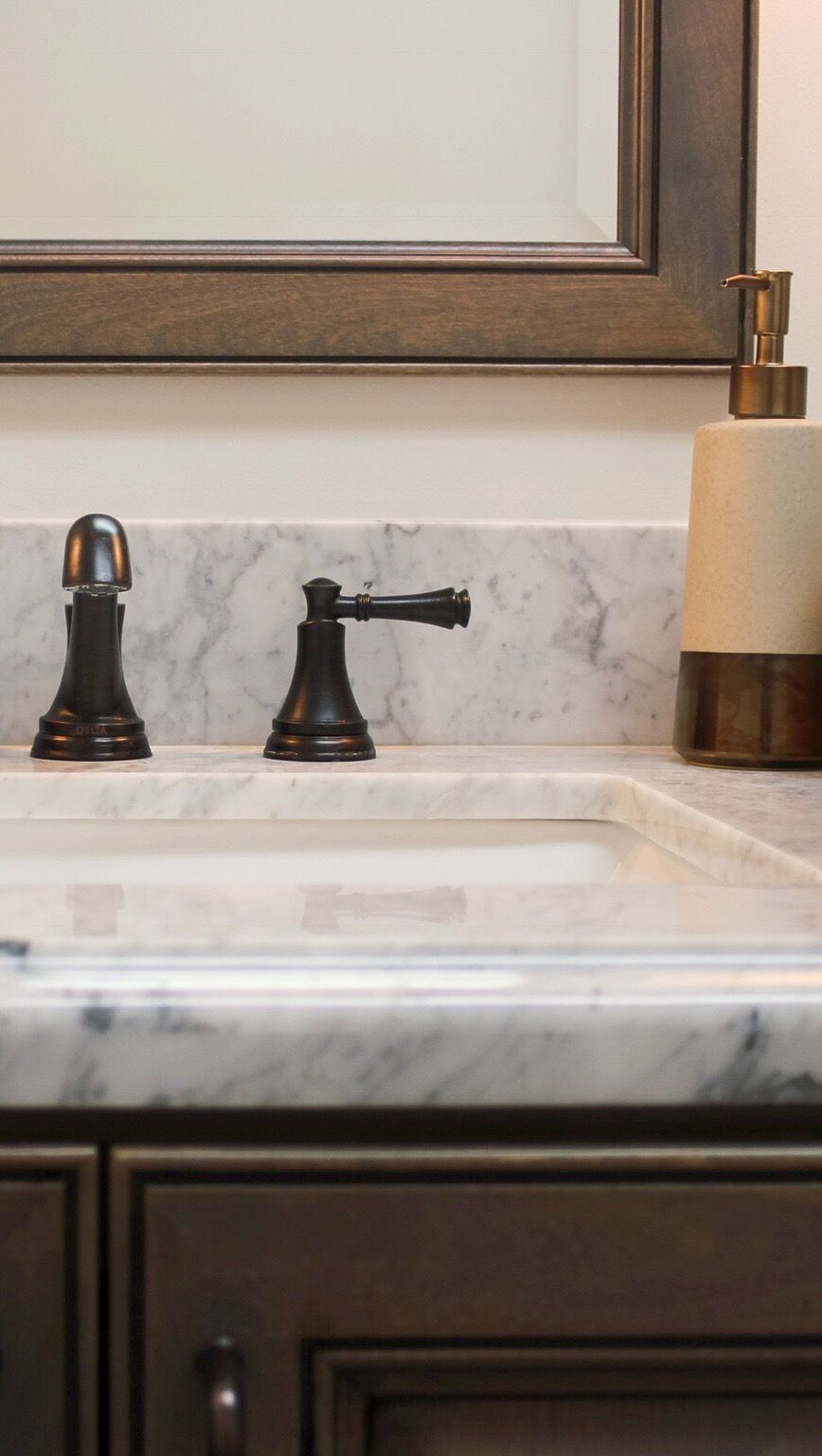 Carrera Marble Countertop With Soft Gray Cabinets And Oil Rubbed