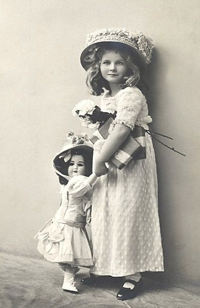 Antique photo of beautiful young girl with her doll.