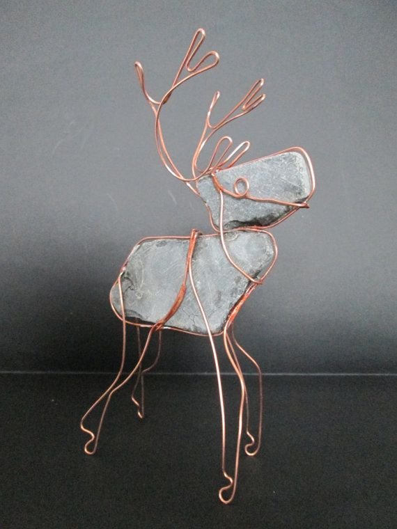 Animal figure made of flat stone and copper wire. The stones are ...