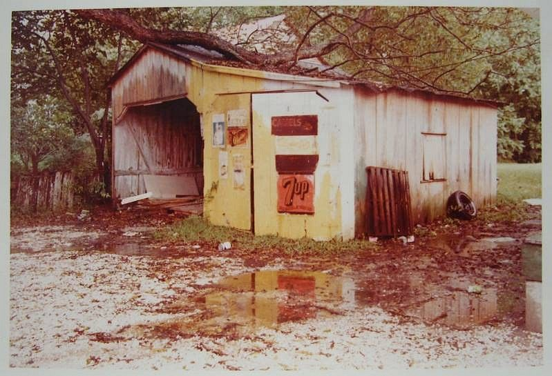 William Eggleston, Untitled (Yellow Garage with Limb on Roof Red 7-Up Sign) 1972