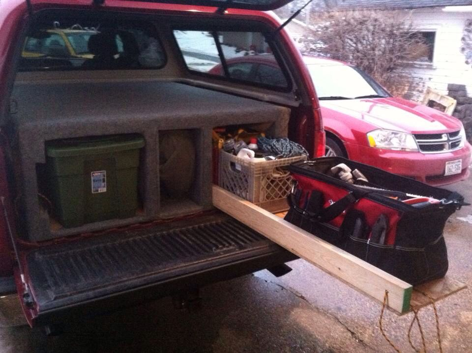 Truck Bed Organizer Fits Three Totes On The Left Full Of Clothes Rock Climbing Gear And Camping Snowboard In Carpeted Middle