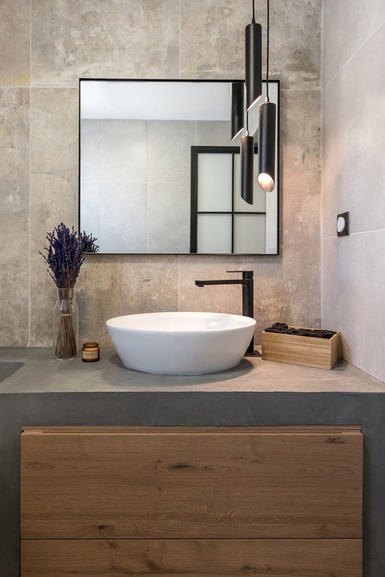 The master bathroom is clad with stone tiles and the vanity is