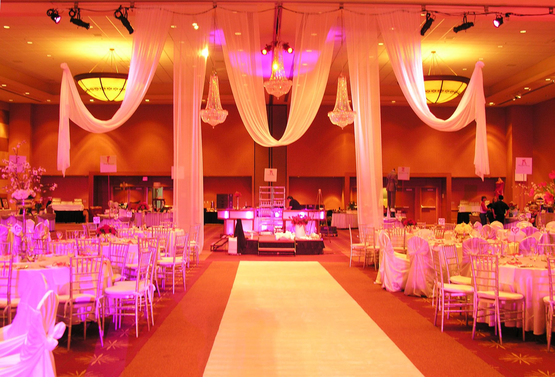 White swag hanging from the ceiling with pink lighting. Formal ...
