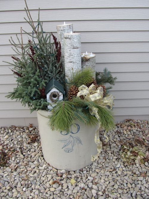 Use a potted mini tree, red bows around wood candle holders-all in a emamelware pot.