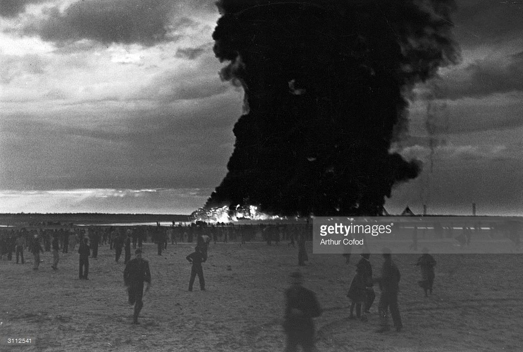 Spectators run from buring wreckage of the Hindenburg