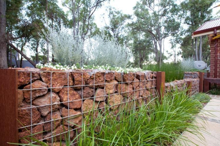 diese gabionen sind mit roten steinen gef llt und dienen On zaun mit steinen