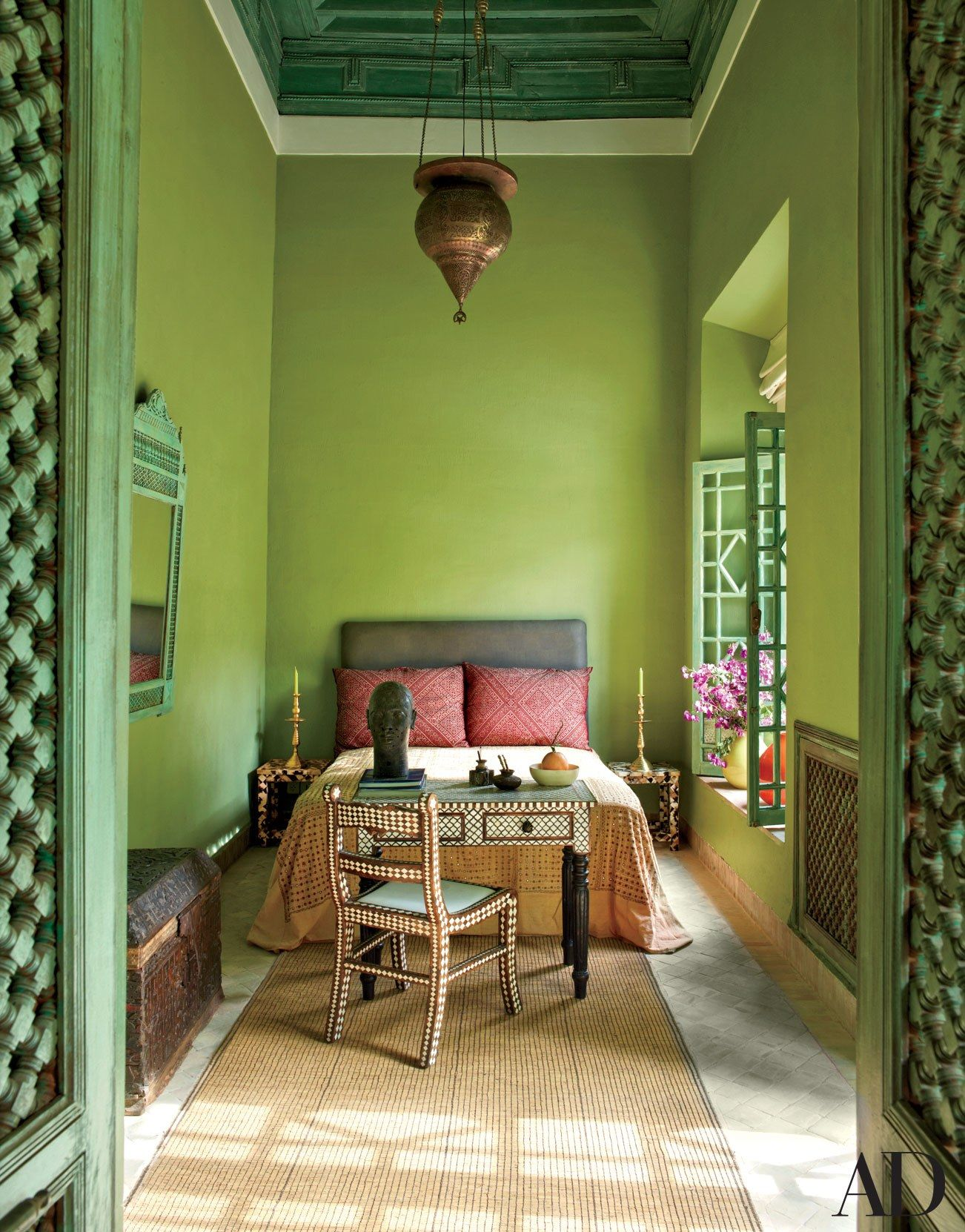 A 19th-century Persian light hangs in the Green Bedroom of a Marrakech riad designed by Chilean artist Claudio Bravo; the bedspread is Gujarati mirrorwork embroidery, the chest is 19th-century Moroccan, and the desk and chair are embellished with bone inlay.
