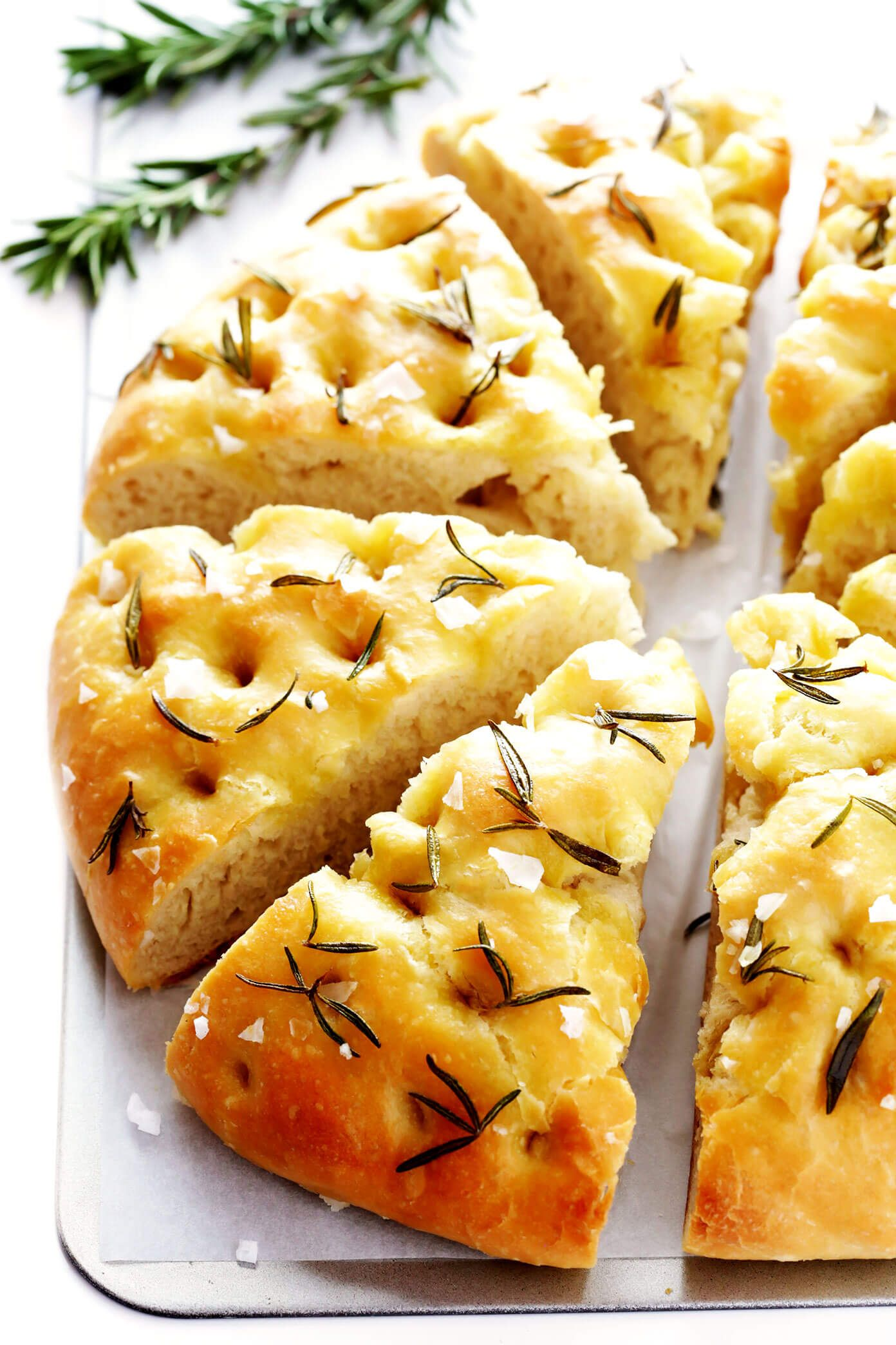 This delicious Rosemary Focaccia Bread recipe is easy to make, and topped with fresh rosemary, olive oil and flaky sea salt. Easy to make as a side for dinner, and it also freezes well! | gimmesomeoven.com #focaccia #bread #italian #side #vegetarian #baking