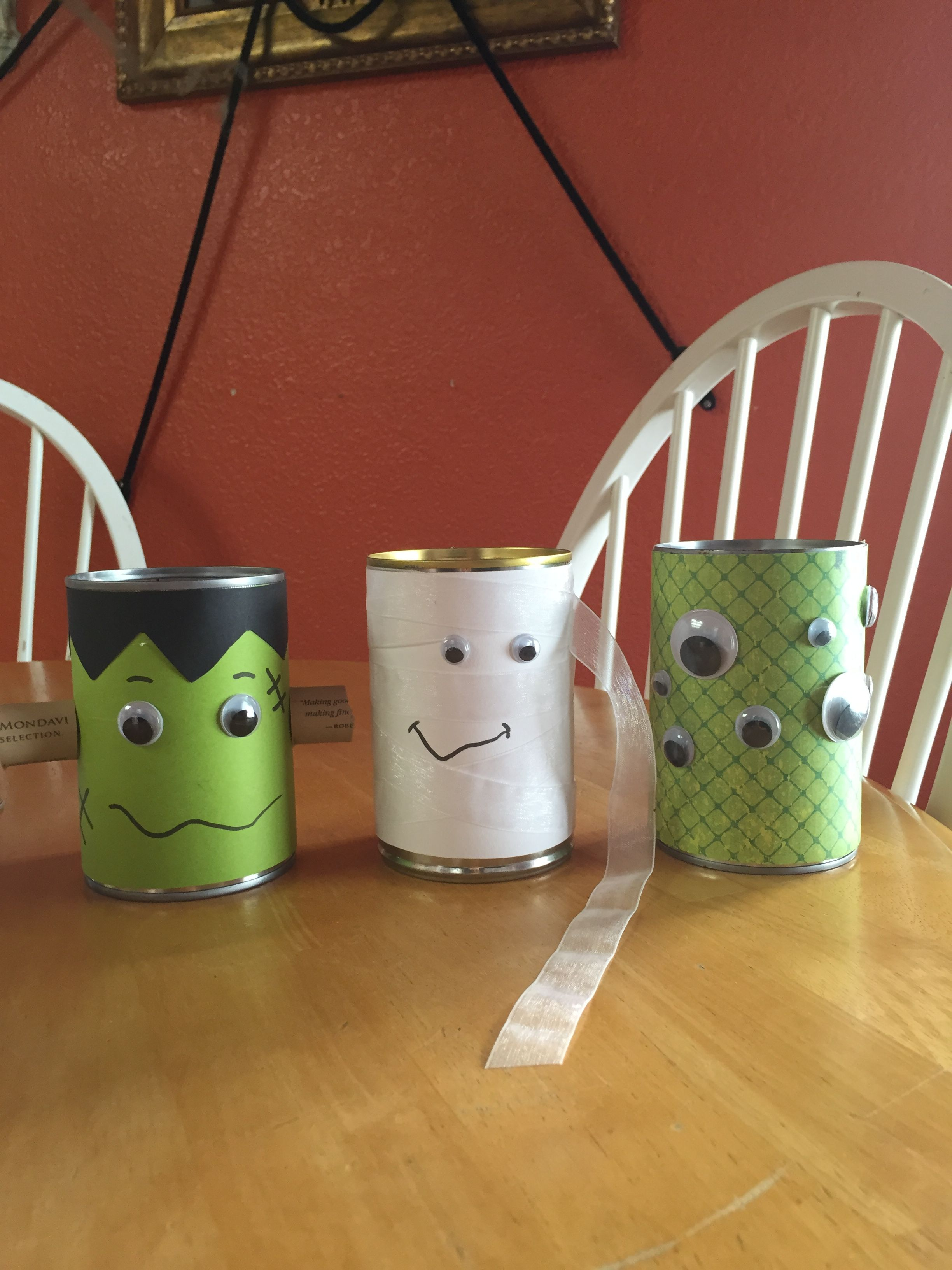 Halloween cutlery holders. I made these out of cans and paperback. I used transparent fabric ribbon for the mummy and Googley eyes on all cans. I also use a wine cork for frankensteins neck piece. I got glued everything on.