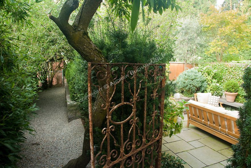 A stone path, leading to an old metal gate, offers entry  into the secluded seating area of this Seattle backyard.  Design by Scot Eckley, I...