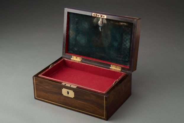 """An English William IV rosewood jewelry box with brass line inlay and brass cartouche and a fitted leather interior.  Circa 1830. 10"""" wide x 6 ½"""" deep x 4 ½"""" high."""