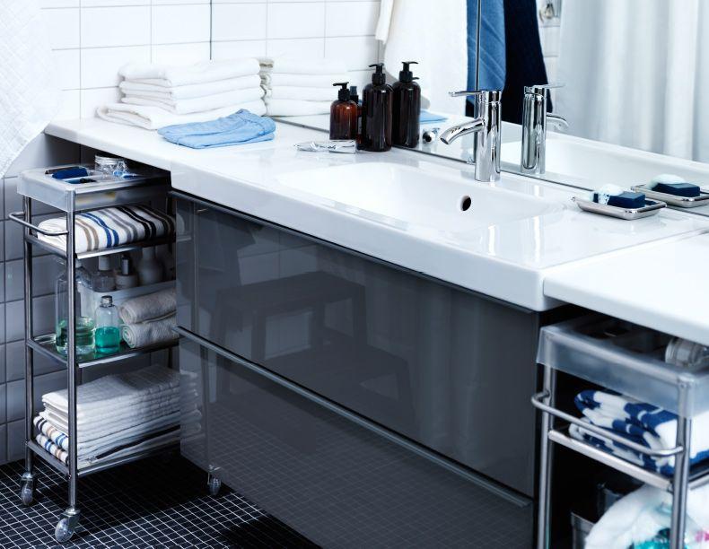 Nahaufnahme von GODMORGON Waschbeckenschrank mit 2 Schubladen Hochglanz grau mit Kosmetik, Handtüchern und Fläschchen zu beiden Seiten