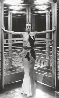 JOAN CRAWFORD Joan Crawford models a gown designed by Adrian for Letty Lynton (1932) in this portrait by George Hurrell takenon the set of G...