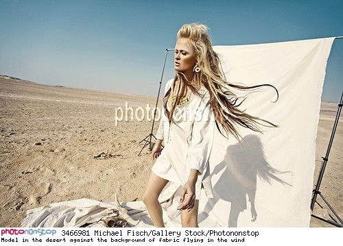 Model in the desert against the background of fabric flying in the wind