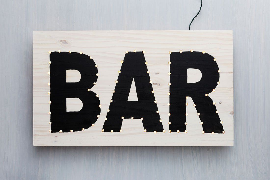 A little over a month ago, Christmas lights were a crucial part of our Christmas decor.Now it might be hard to remember what box they are tucked away in. Hope you can find them, because those lights canbe used for several other purposes throughout the year,like this adorable DIY light sign for your home bar …