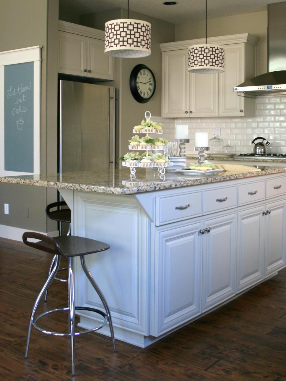 White cabinets and kitchen island complement the white tile ...