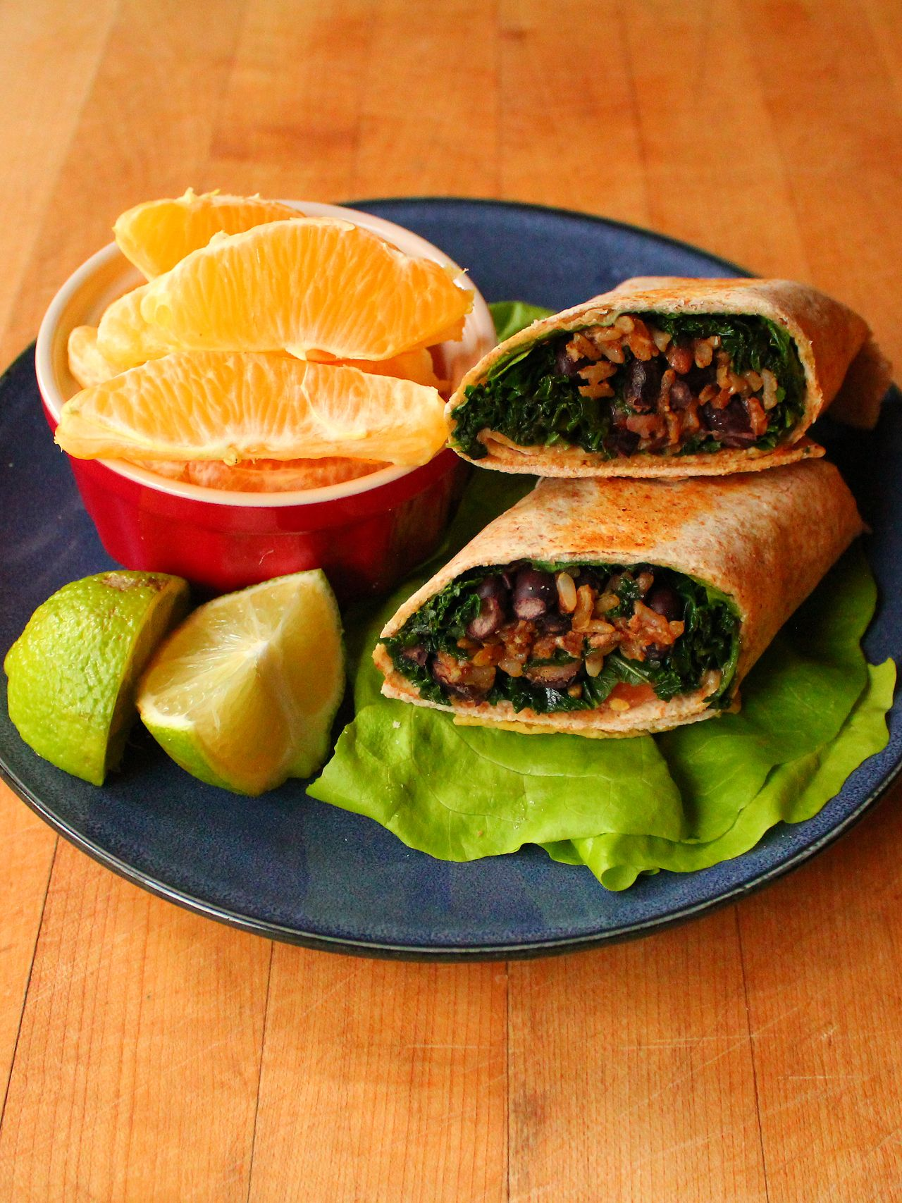 Seasoned brown rice, black bean, and kale burrito on a whole wheat tortilla with butter lettuce, tomato, and lime. Peeled navel orange...