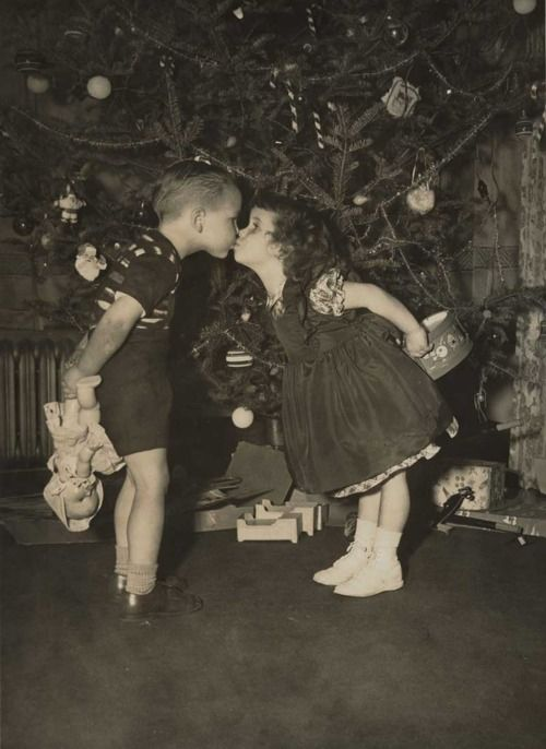 Children share a Christmas kiss in front of a tree before exchanging ...