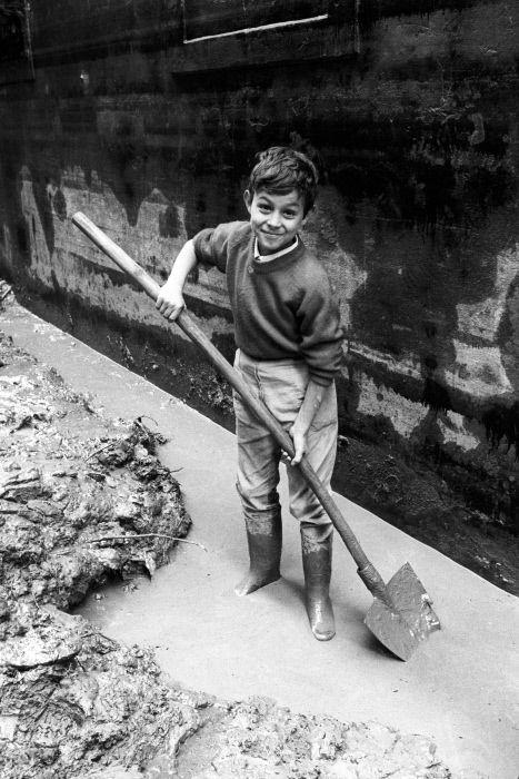 A child posing while he is making his contribution to the cleaning of a flooded street. Florence, 1966. MONDADORI PORTFOLIO/Giorgio Lotti/Mario De Biasi/Sergio Del Grande