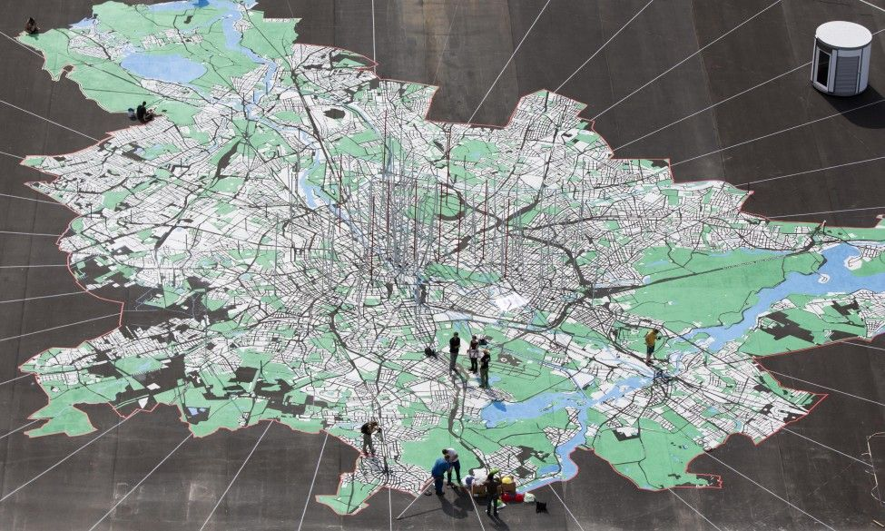 Artists work on a giant city map of Berlin on a concrete square in Berlin, Germany.  (AP)
