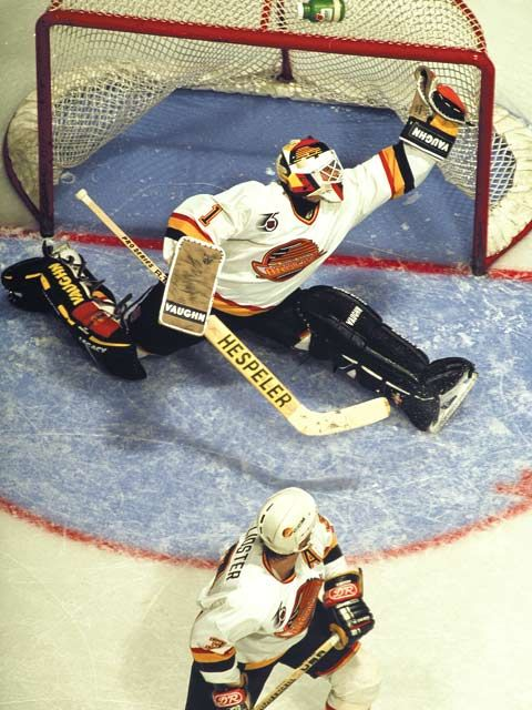 Kirk McLean makes a glove save and Doug Lidster watches.  f9837f118