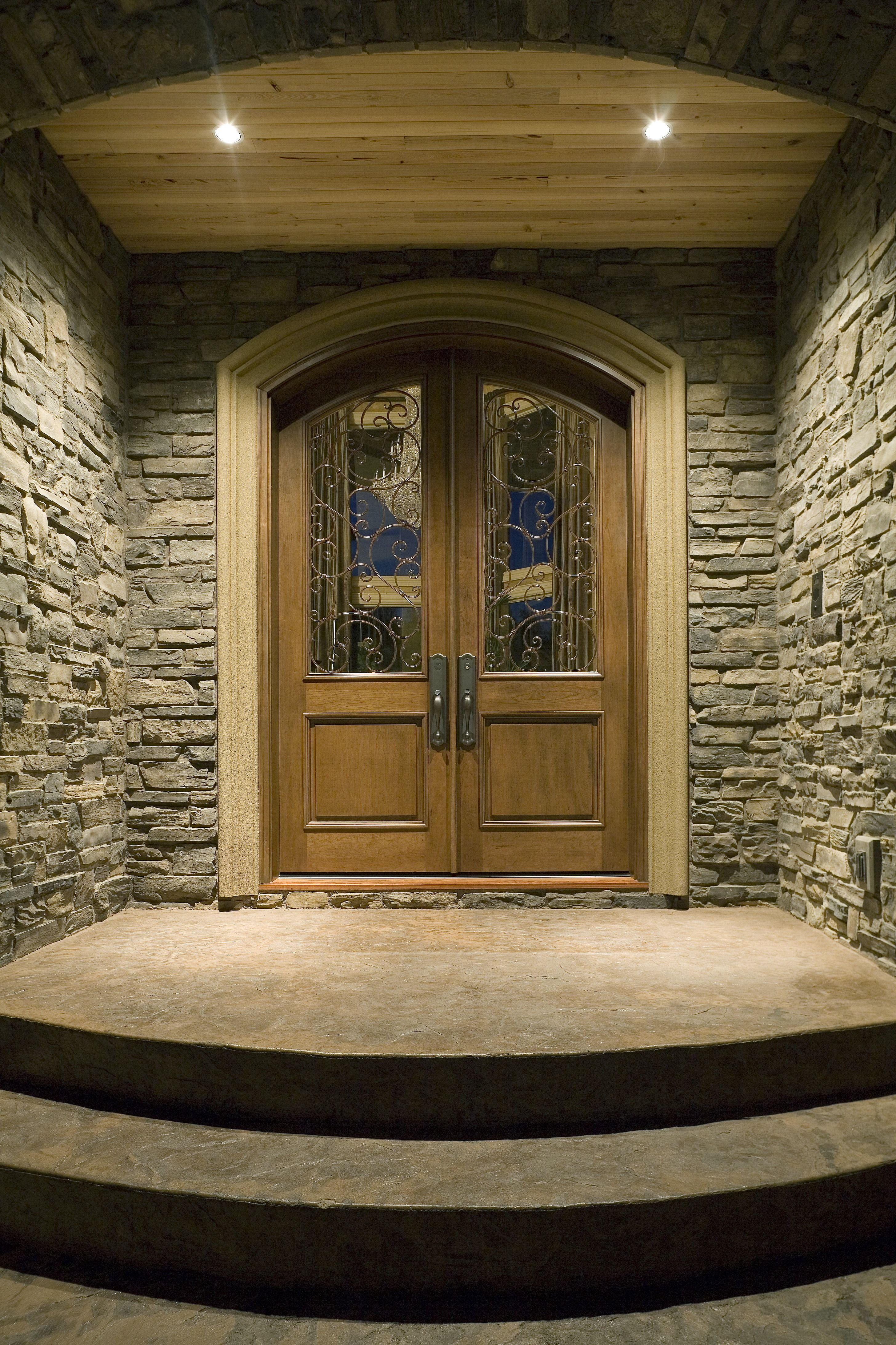 Quite The Entry With Stone Siding Double Doors Concrete Frame Hardwood Ceiling And Recessed Lights To Give Any Suburban Home Evening View They